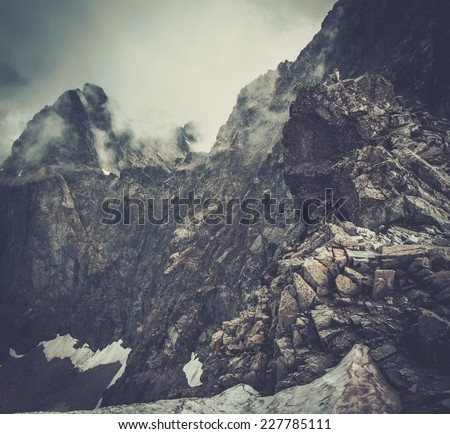 Woman hiker sitting on a mountain peak  - stock photo