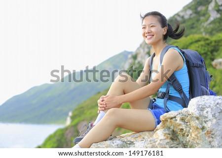 woman hiker smile/sit on seaside mountain rock - stock photo