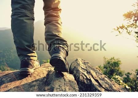 woman hiker stand on mountain peak rock  - stock photo