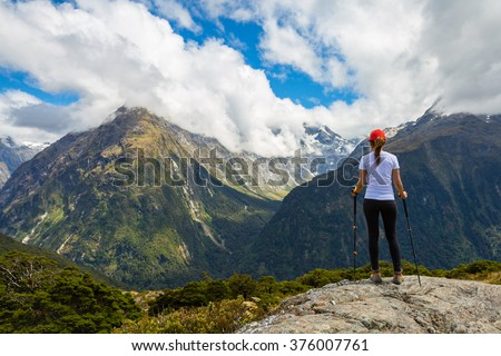 Woman hiker standing on a cliff and enjoys the view of Key Summit with Ailsa Mountain at the background. Routeburn Track, New Zealand - stock photo
