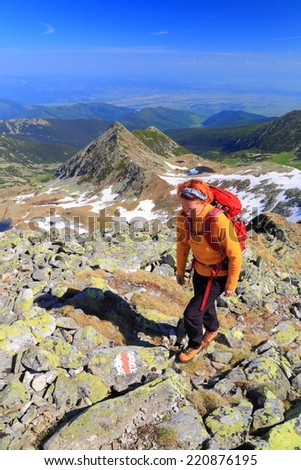 Woman hiker surrounded by granite boulders on sunny mountain
