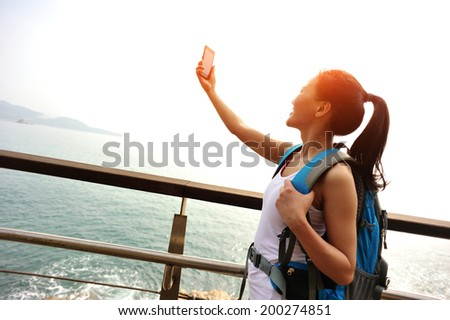 woman hiker taking self photo on sunrise seaside - stock photo
