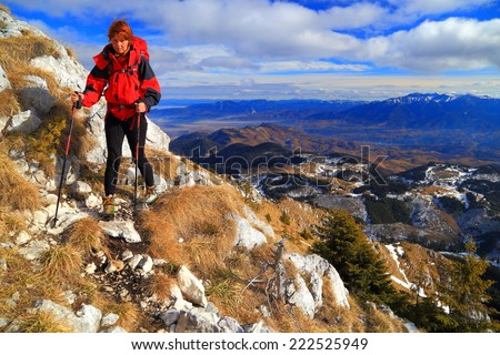 Woman hiker traverses a narrow trail on the mountain top - stock photo