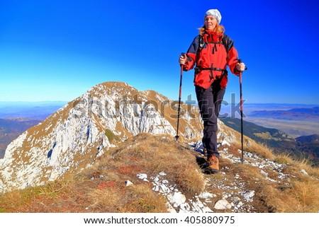 Woman hiker traversing a mountain ridge under the blue sky - stock photo