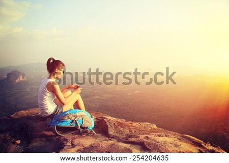 woman hiker use her cellphone at sunset mountain peak cliff - stock photo