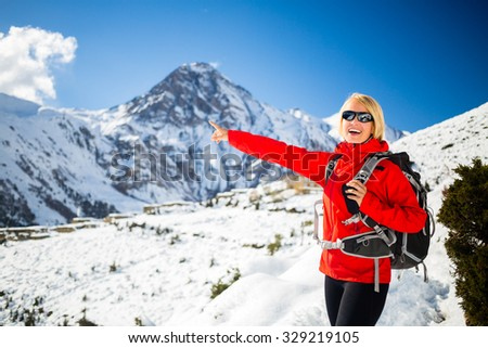 Woman hiker walking, looking and pointing at beautiful inspirational winter mountains. Trekking and hiking inspiration and motivation outdoors. Travel and healthy lifestyle in Himalayas, Nepal. - stock photo