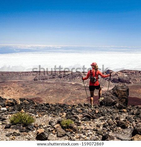 Woman hiker walking trekking in summer mountains. Young female on rocky mountain ridge looking at beautiful view. Hiking on volcano mountain over clouds, Tenerife Canary Islands