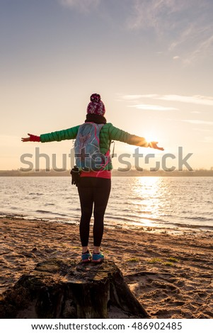 Woman hiker with arms outstretched enjoying sunrise and lake, relaxing on beach and sand. Happy female celebrating beautiful morning with backpack looking at inspirational landscape on beach.