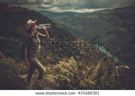 Woman hiker with backpack drinking fresh water from a bottle on a top of mountain. - stock photo