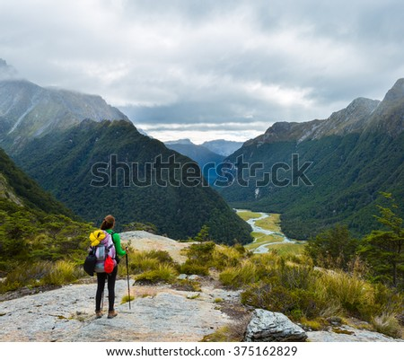 woman hiker with backpack looking at the view of Routeburn Flat from Routeburn Falls, New Zealand - stock photo
