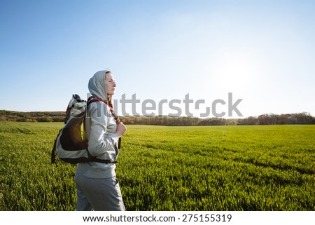 woman hiker with backpack walking through the grass meadow
