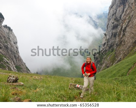 woman hiking above a green valley with swirling clouds framed by rocky mountain walls - stock photo
