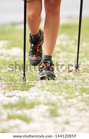 Woman hiking and nordic walking in forest. Sport shoe close up - stock photo