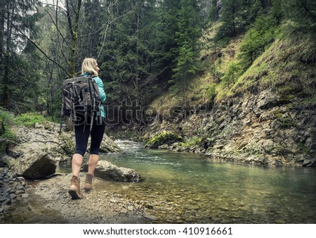Woman hiking around mountains near the river at spreeng time. - stock photo