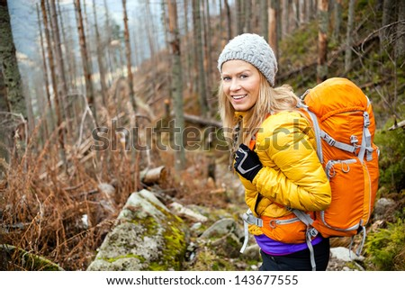 Woman hiking in autumn forest in mountains. Recreation and healthy lifestyle outdoors in nature. Beauty blond looking at camera smiling. - stock photo
