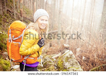 Woman hiking in autumn forest in mountains. Trekking, recreation and healthy lifestyle outdoors in nature. Beauty blond backpacker looking at camera smiling, bright light sunlight in background. - stock photo