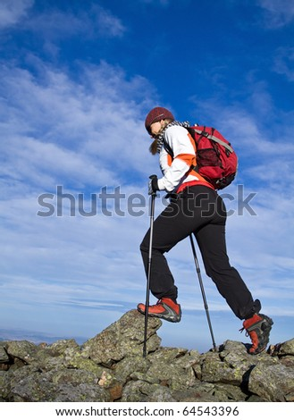 Woman hiking in Autumn mountains, nordic walking and backpacking.