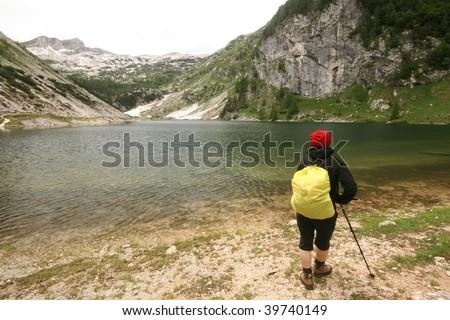 Woman hiking in bad weather in alps near lake - stock photo