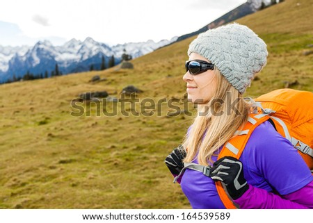 Woman hiking in beautiful mountains with backpack. Recreation and healthy lifestyle outdoors in nature. Beauty blond hiker looking at mountain view on sunset. - stock photo