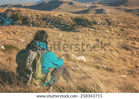 Woman hiking in beautiful nature, back light by morning sunlight rays, recreation and healthy lifestyle outdoors in wild. Hiker backpacker sitting on mountain top. - stock photo