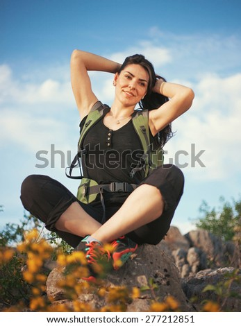 Woman hiking in beautiful nature, back light by morning sunlight rays, recreation and healthy lifestyle outdoors in wild. Hiker backpacker walking on mountain top. - stock photo