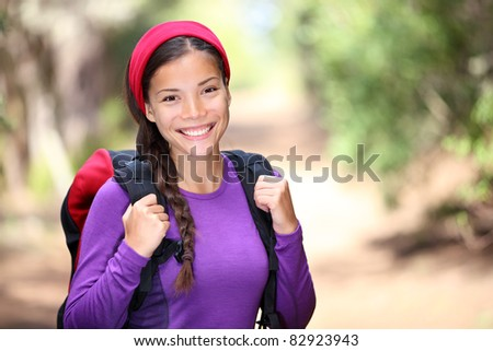 Woman hiking in forest. Female hiker smiling happy portrait on beautiful sunny day during a trekking trip. Pretty young Asian woman model outdoors in nature. - stock photo
