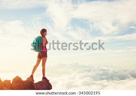 Woman Hiking in the Mountains Above the Clouds at Sunset, Adventure Outdoor Active Lifestyle - stock photo