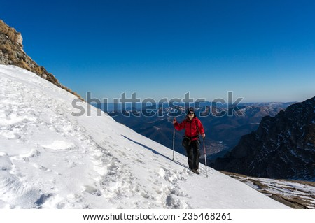 Woman hiking in the mountains in winter in Romania, Bucegi mountains, Carpathians - stock photo