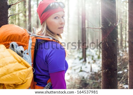Woman hiking in white winter forest, backlight by morning sunlight rays, recreation and healthy lifestyle outdoors in nature. Beauty blond hiker backpacker looking at camera on sunset. - stock photo