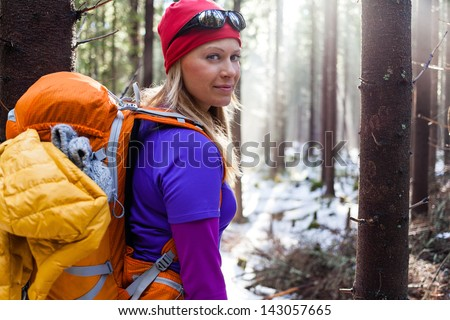 Woman hiking in white winter forest. Recreation and healthy lifestyle outdoors in nature. Beauty blond looking at camera on sunset. - stock photo