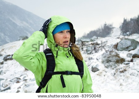 Woman hiking in winter mountains. Snowing and cold on trekking. - stock photo