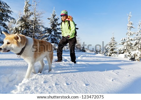 Woman hiking in winter mountains with akita dog, walking on white snow. Sport and fitness in wilderness nature outdoors. Beautiful female hiker with canine. - stock photo