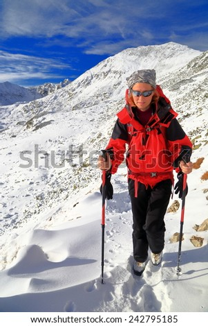 Woman hiking on snow covered mountain during winter - stock photo