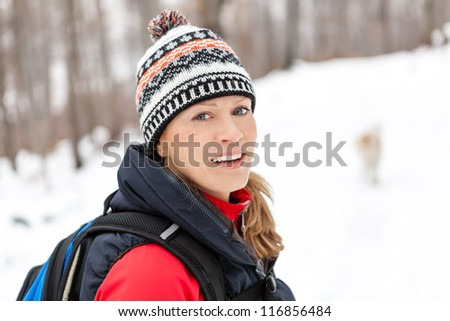 Woman hiking on snow in white winter forest. Recreation and healthy lifestyle outdoors in nature. Beauty blond looking at camera on sunset.