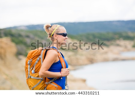 Woman hiking on trail with backpack at seaside on island. Recreation and healthy lifestyle outdoors in summer mountains. Trekking and activity concept in beautiful inspirational landscape. - stock photo