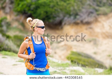 Woman hiking on trail with backpack in mountains. Recreation and healthy lifestyle outdoors in summer mountains. Trekking and activity concept in beautiful inspirational landscape. - stock photo