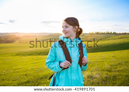 Woman hiking portrait. Fresh and healthy female model during hike outdoors in field. - stock photo