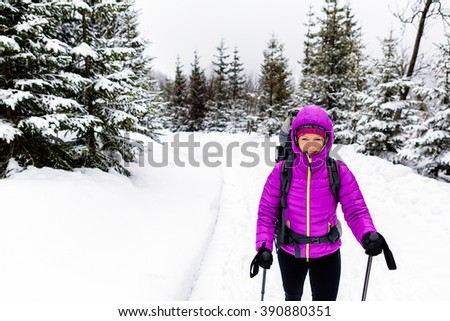 Woman hiking trekking in winter woods with backpack. Recreation fitness and healthy lifestyle outdoors in nature. Motivation and inspirational white winter landscape. - stock photo