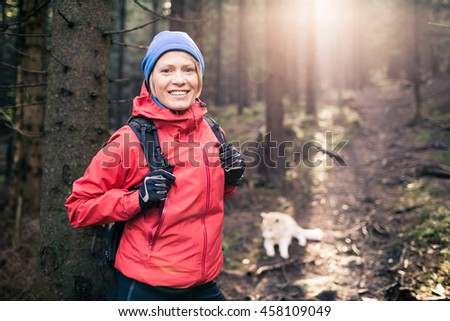 Woman hiking with akita inu dog on forest trail. Recreation and healthy lifestyle outdoors, autumn woods in mountains, inspirational nature. Fitness and trekking and activity concept. - stock photo
