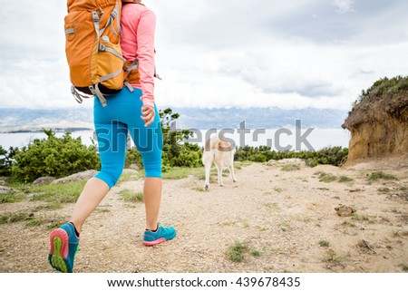 Woman hiking with akita inu dog on seaside trail. Recreation and healthy lifestyle outdoors in summer mountains and sea nature. Beautiful inspirational landscape. Trekking and activity concept. - stock photo