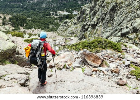 Woman hiking with backpack in Corsica mountains, trekking and outdoors activity, France - stock photo