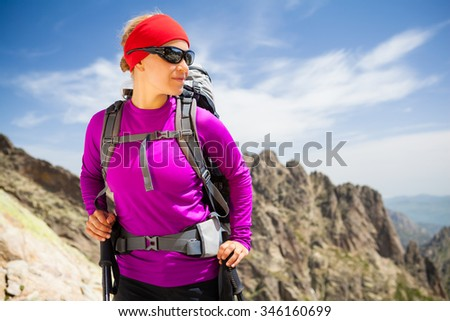 Woman hiking with backpack in inspirational mountains. Female caucasian trekker hiker tourist looking from mountain top to beautiful scenic view. Sport and fitness in nature, Corsica France - stock photo