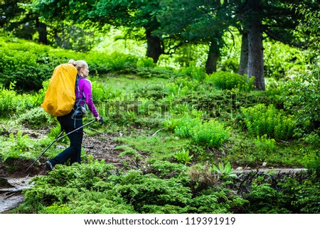 Woman hiking with backpack in mountains, Corsica, France. Adventure in summer wilderness nature outdoors, healthy lifestyle trekking and walking. - stock photo