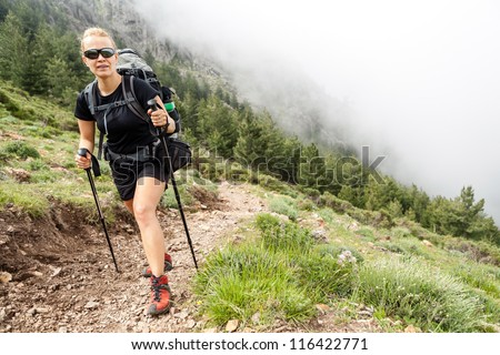 Woman hiking with backpack in mountains, trekking Corsica, France - stock photo