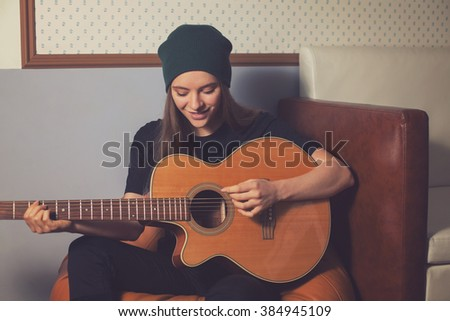 Woman hipster playing on guitar and enjoying music