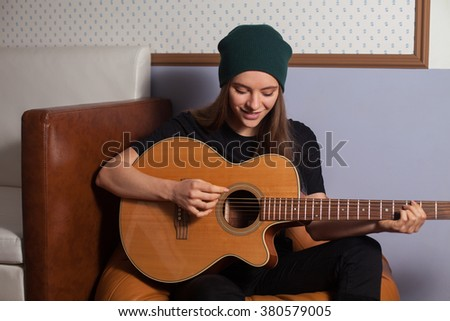 Woman hipster playing on guitar and singing