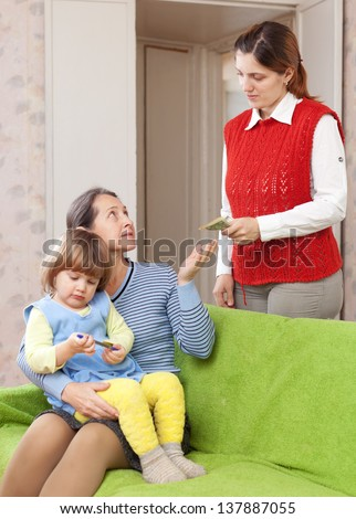 Woman hires babysitter for her child at home. Focus on adults - stock photo