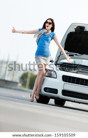 Woman hitchhiking near the opened bonnet of the broken car and waiting for assistance