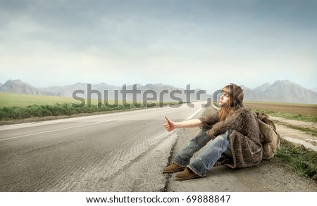 Woman hitchhiking on a countryside road - stock photo