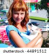 Woman hold a white kitten. Face view. - stock photo